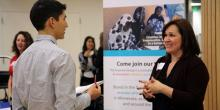 Samantha speaks to visitors who are interested in learning more about The Improve Group at an Exhibitor booth at the University of Minnesota's career fair